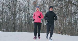 Homem novo e mulher em uma manhã corrida na floresta do inverno uma mulher em um revestimento que fraco um homem em um revestimen filme