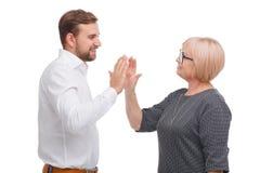 Homem novo e mulher mais idosa que dão uns cinco entre si fotografia de stock royalty free