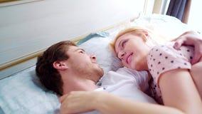 Homem novo e mulher na cama no desgaste da noite que sorriem em se na manhã