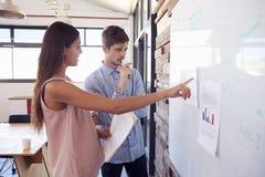 Homem novo e mulher na discussão no whiteboard em um escritório fotografia de stock