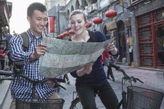Homem novo e mulher nas bicicletas, olhando o mapa. Imagens de Stock