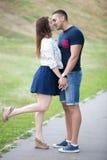 Homem novo e mulher que beijam no parque foto de stock