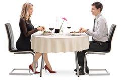 Homem novo e mulher que comem em uma data foto de stock