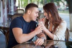 Homem novo e mulher que compartilham da bebida em um café fotografia de stock royalty free