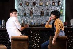 Homem novo e mulher que conversam na barra fotos de stock