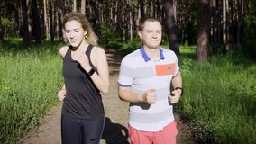 Homem novo e mulher que correm junto em madeiras do verde do verão filme