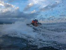 Homem novo e mulher que derivam através da superfície do mar Os povos em Jet Ski têm o divertimento no oceano Motorista na ação d foto de stock royalty free