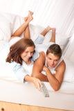 Homem novo e mulher que encontram-se para baixo na sala de estar Imagens de Stock
