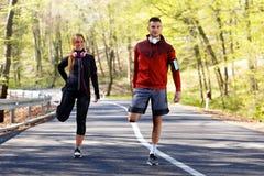 Homem novo e mulher que esticam os músculos na estrada antes do corredor fotografia de stock