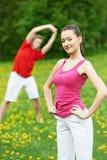 Homem novo e mulher que fazem esticando exercícios Imagem de Stock Royalty Free