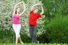 Homem novo e mulher que fazem esticando exercícios Fotos de Stock