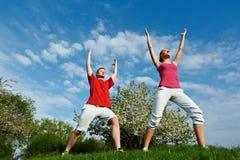 Homem novo e mulher que fazem esticando exercícios Imagens de Stock