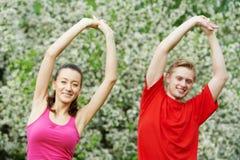 Homem novo e mulher que fazem esticando exercícios Foto de Stock Royalty Free