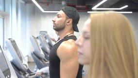 Homem novo e mulher que fazem o cardio- exerc?cio na escada rolante no gym filme