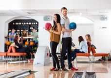 Homem novo e mulher que guardam bolas de boliches no clube Imagens de Stock Royalty Free