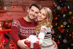 Homem novo e mulher que guardam um presente envolvido fotografia de stock