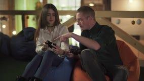 Homem novo e mulher que jogam o jogo de v?deo que senta-se em cadeiras confort?veis no caf? Os pares bonitos t?m uma data e um di video estoque