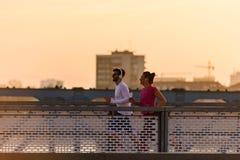 Homem novo e mulher que movimentam-se junto sobre a ponte no por do sol ou no nascer do sol imagens de stock