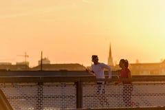 Homem novo e mulher que movimentam-se junto sobre a ponte no por do sol ou no nascer do sol fotografia de stock