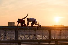 Homem novo e mulher que movimentam-se junto sobre a ponte no por do sol ou no nascer do sol imagens de stock royalty free
