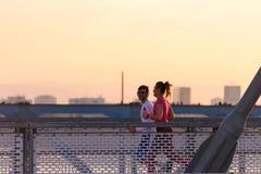 Homem novo e mulher que movimentam-se junto sobre a ponte no por do sol ou no nascer do sol fotos de stock