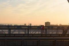 Homem novo e mulher que movimentam-se junto sobre a ponte no por do sol ou no nascer do sol imagem de stock royalty free
