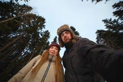 Homem novo e mulher que olham assombradamente à câmera na floresta do inverno fotografia de stock