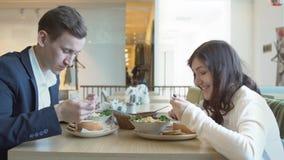 Homem novo e mulher que têm o almoço em um café video estoque