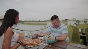Homem novo e mulher que têm o almoço em um restaurante no terraço exterior vídeos de arquivo