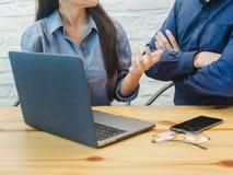 Homem novo e mulher que trabalham no escritório Mulher de negócio que explica o projeto ao homem de negócio Coworking, trabalhos  imagens de stock