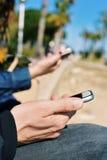 Homem novo e mulher que usa seus smartphones Fotografia de Stock Royalty Free
