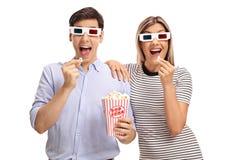 Homem novo e mulher que vestem os vidros 3D e que comem a pipoca Foto de Stock Royalty Free