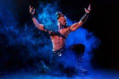 Homem novo e muscular que executa uma pose teatral na fase Foto de Stock