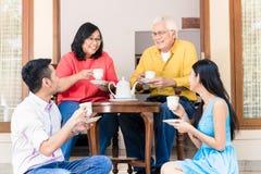 Homem novo e pais de visita da mulher em casa na tarde imagem de stock royalty free