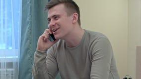 Homem novo e saudável que sorri e que fala no telefone esperto em casa Foto de Stock