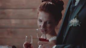 Homem novo e seu vinho bonito da bebida da menina durante o jantar em um restaurante, close-up video estoque