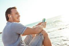 Homem novo e sorrindo que senta-se com smartphone móvel imagem de stock