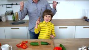 Homem novo e suas mãos de aplauso do filho junto na cozinha após ter cortado o pepino Pai e filho que desbastam vegetais vídeos de arquivo
