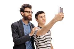 Homem novo e um adolescente que toma um selfie junto fotografia de stock