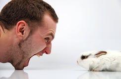 Homem novo e um coelho no fundo branco Imagem de Stock