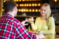 Homem novo e vinho bebendo da mulher em um restaurante Homem novo e vinho bebendo da mulher em uma data Homem e mulher em uma dat fotos de stock