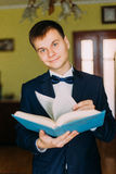 Homem novo elegante com o laço que guarda um livro e que olha a câmera Sala de hotel no fundo fotografia de stock royalty free