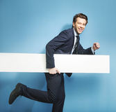 Homem novo elegante que corre com a placa Foto de Stock Royalty Free