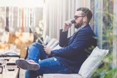 Homem novo elegante que senta-se na cafetaria e que guarda o dispositivo digital da tabuleta foto de stock royalty free