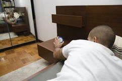 Homem novo em acordar da cama, desligando o despertador imagens de stock