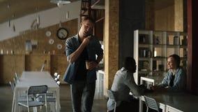 Homem novo em caminhadas ocasionais em um escritório ou em um local de trabalho moderno com interior do estilo do tijolo ao falar video estoque