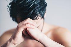 Homem novo em rezar da dor imagens de stock