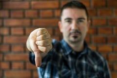 Homem novo em seu 30s que mostra os polegares para baixo Foco seletivo fotografia de stock royalty free