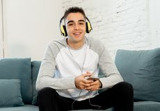 Homem novo em seus anos 20 com fones de ouvido que escuta a música e que dança ao relaxar em casa imagens de stock