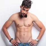 Homem novo em topless com mãos nos quadris Fotografia de Stock Royalty Free